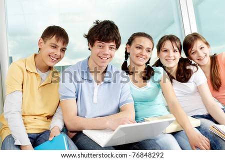 Portrait of five teens sitting with laptop, looking at camera and smiling