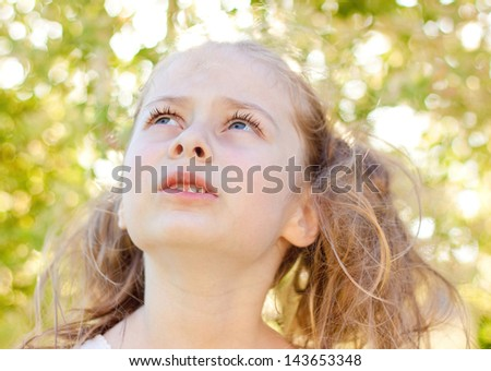 Portrait of five years old caucasian blond child girl in the garden looking up - stock photo