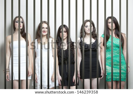 Portrait of five young women standing side by side behinds prison bars - stock photo