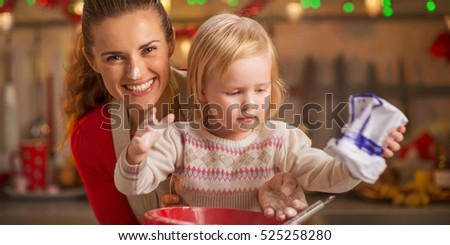 Portrait of flour smeared mother and baby making christmas cookies