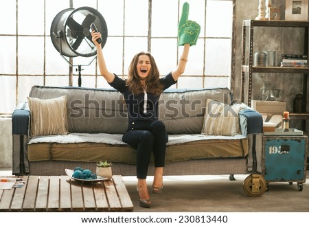 Portrait of football fan woman watching tv in loft apartment and rejoicing - stock photo