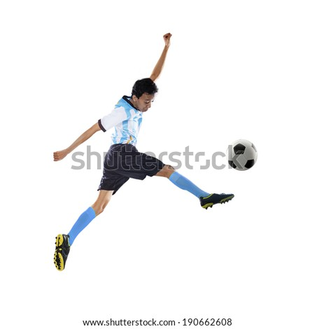 Portrait of football player kicking ball while jumping isolated on white - stock photo