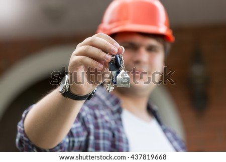 Portrait of foreman in hardhat giving keys of new house - stock photo