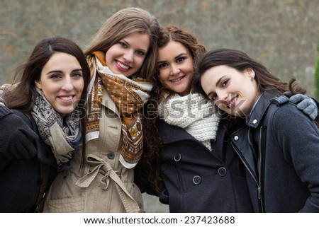 Portrait of four attractive young women, smiling and embracing  - stock photo