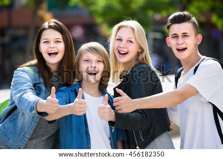 Portrait of four cheerful european teenagers standing and holding thumbs up together outdoors