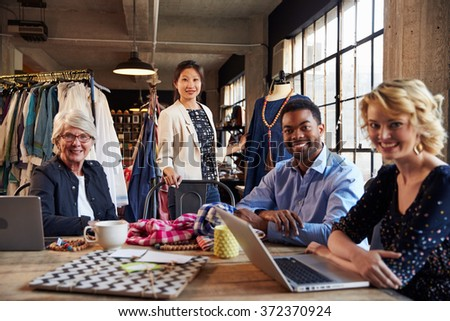 Portrait Of Four Fashion Designers In Meeting - stock photo
