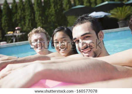 Portrait of four friends in pool with inflatable raft