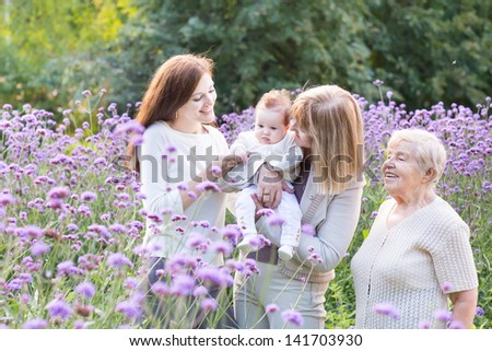 Portrait of four generation of beautiful women relaxing in the g - stock photo