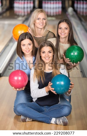Portrait of four happy women in bowling with colored balls.