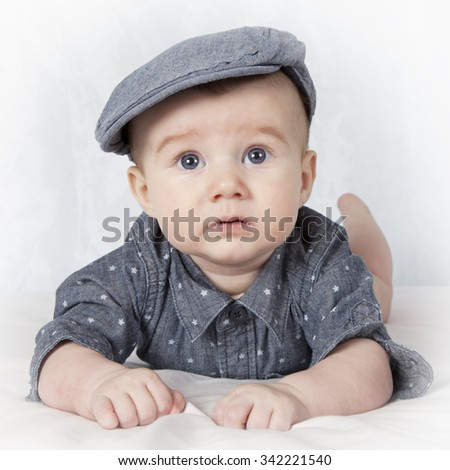 Portrait of four months old baby boy lying on his tummy  - stock photo