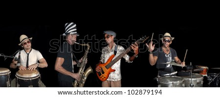 Portrait of four musicians playing isolated against black background - stock photo