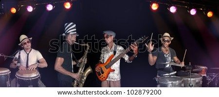 Portrait of four musicians playing on stage against black background - stock photo