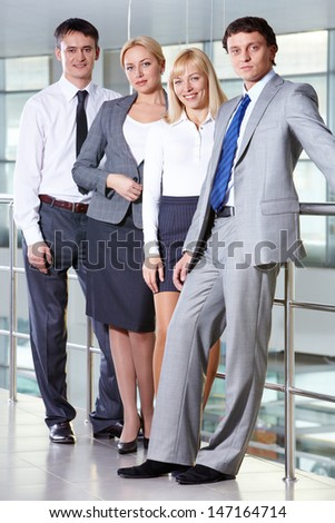 Portrait of four smiling business people looking at camera - stock photo