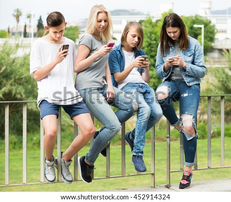 Portrait of four smiling spanish teenagers sitting with their mobile phones outdoors in town - stock photo