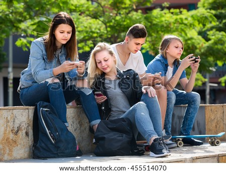 Portrait of four smiling teenagers sitting with their mobile phones outdoors in town - stock photo