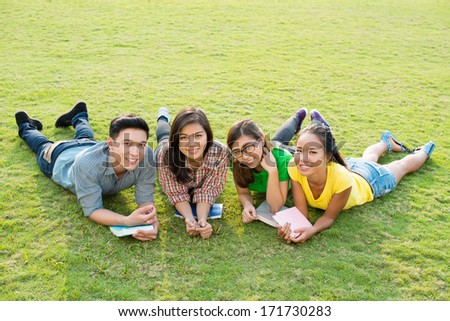 Portrait of four students posing on lawn