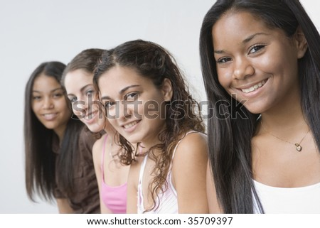 Portrait of four teenage girls smiling against white background.