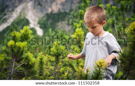 Portrait of four year old boy walking outdoors in the mountains. Dolomites, Italy. - stock photo