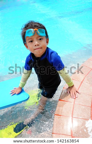 Portrait of four years old boy with swimming accessories - stock photo