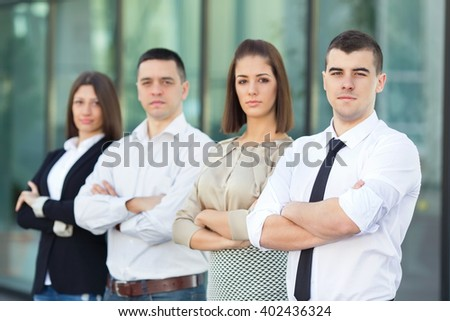 Portrait of four young and successful business people. Focus on confident young businessman standing with his arms crossed in front of his business team. - stock photo