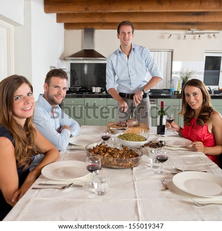 Portrait of Four young friends enjoying a dinner at home