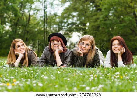 Portrait of four young girls lying down in the park and enjoy in nature.Happy girls - stock photo