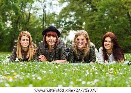 Portrait of four young girls lying down in the park and looking at camera.Friendship - stock photo