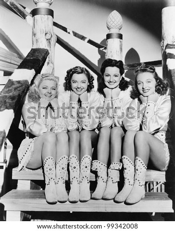 Portrait of four young women sitting on steps in western clothing - stock photo