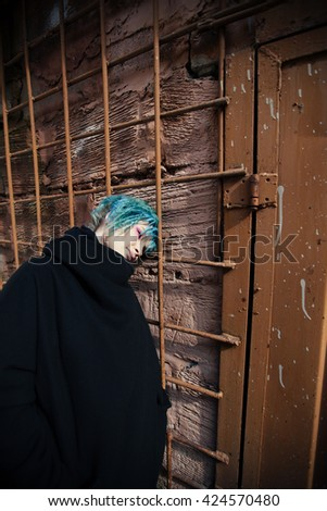 Portrait of freaky young girl with blue hair outdoors