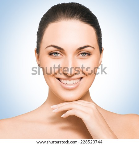 Portrait of Fresh and Beautiful brunette woman against blue background. - stock photo