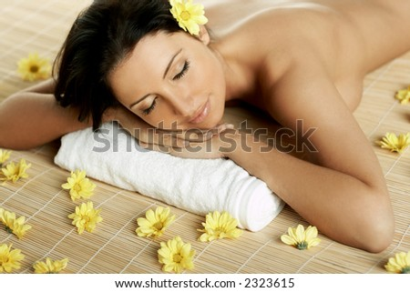 Portrait of Fresh and Beautiful brunette woman laying on bamboo mat around yellow flowers