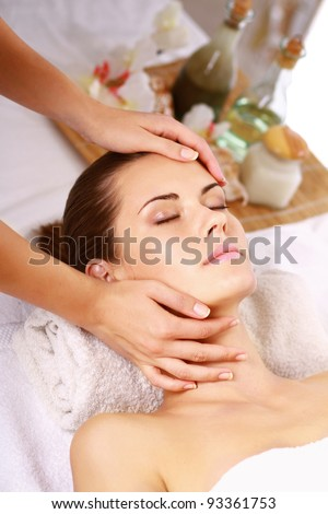Portrait of fresh and beautiful brunette woman taking head massage - stock photo