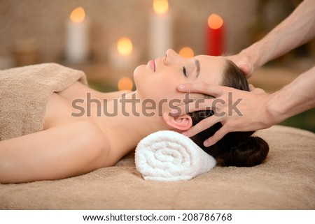 Portrait of Fresh and Beautiful brunette woman taking head massage isolated on background spa salon - stock photo