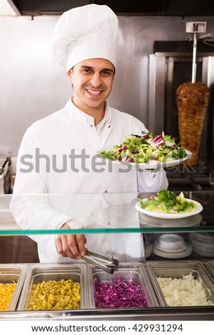 Portrait of friendly adult male chef with kebab at fastfood place - stock photo