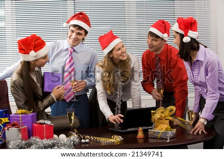 Portrait of friendly business team wearing Santa caps while communicating in office - stock photo