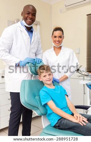 portrait of friendly dental team with little patient - stock photo