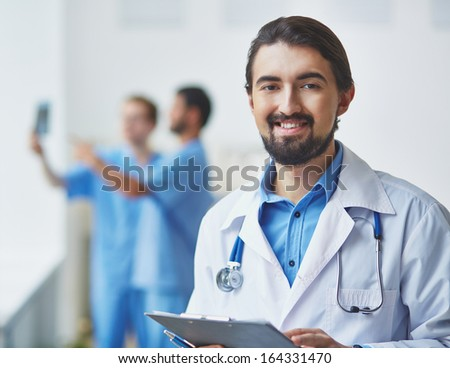 Portrait of friendly doctor looking at camera on background of his colleagues interacting - stock photo