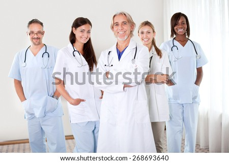 Portrait of friendly doctors with folded hands standing together smiling at camera - stock photo