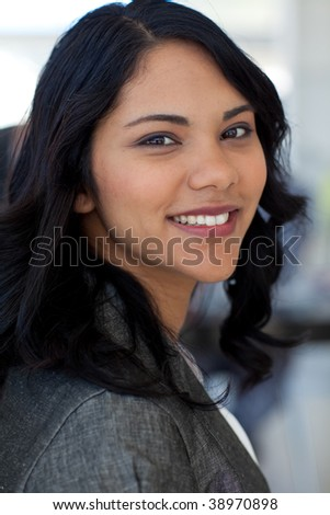 Portrait of friendly ethnic businesswoman in office smiling at the camera