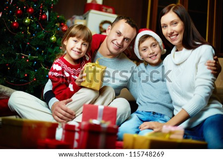 Portrait of friendly family looking at camera on Christmas evening