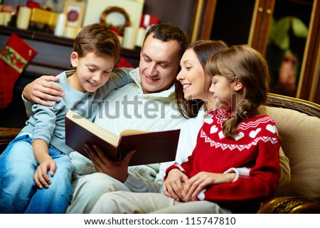 Portrait of friendly family reading book on Christmas evening - stock photo