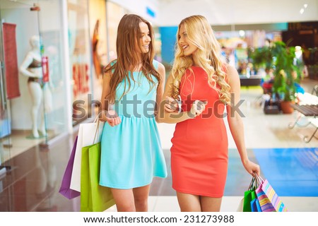 Portrait of friendly girls with paperbags talking while walking in the mall - stock photo