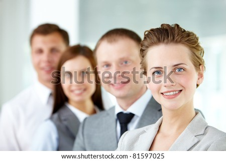 Portrait of friendly leader looking at camera with three employees behind