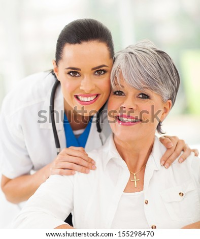 portrait of friendly medical nurse and senior patient - stock photo