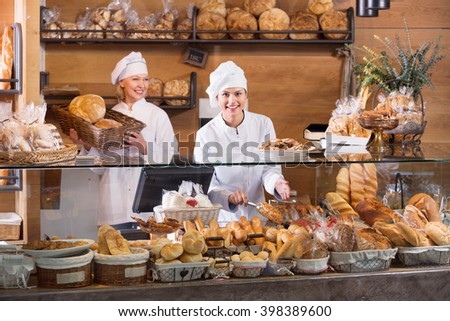 Portrait of friendly  positive women at bakery display with pastry - stock photo