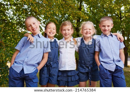 Portrait of friendly pupils looking at camera outside - stock photo