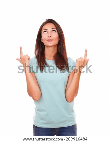 Portrait of friendly 30s woman on blue t-shirt pointing up her fingers while looking above and standing on isolated white background - copyspace - stock photo