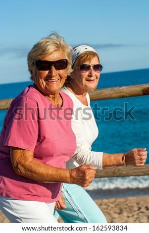 Portrait of friendly senior ladies in casual sportswear outdoors. - stock photo