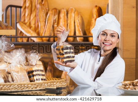 Portrait of friendly smiling charming woman at bakery display with pastry - stock photo