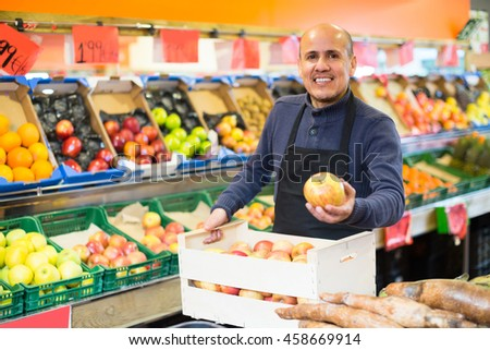 Portrait of friendly smiling mature man in apron selling seasonal fruits at market